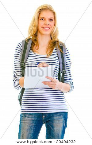 Smiling teengirl with schoolbag writing in notebook isolated on white