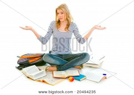 Teengirl with surprise expression on face sitting on floor surrounded by books isolated on white
