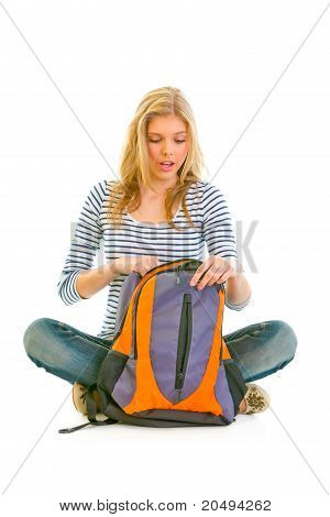 Teen girl sitting on floor and searching something in schoolbag isolated on white