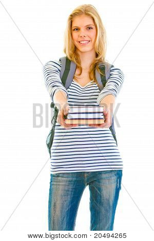 Smiling teen girl with schoolbag giving books isolated on white
