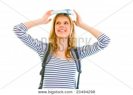 Cheerful teen girl balancing book on top of her head isolated on white