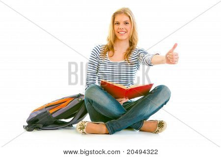Showing thumbs up gesture smiling young girl with schoolbag and book sitting on floor isolated