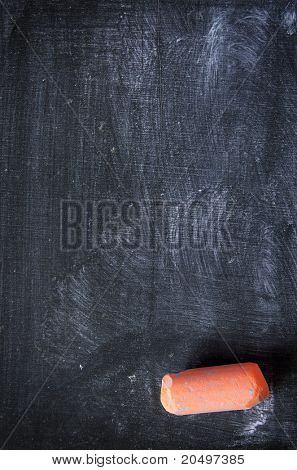 Dirty and used blackboard and a piece of colored chalk
