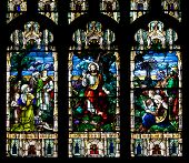 foto of stained glass  - Stained glass windows at church reflecting religious figures - JPG