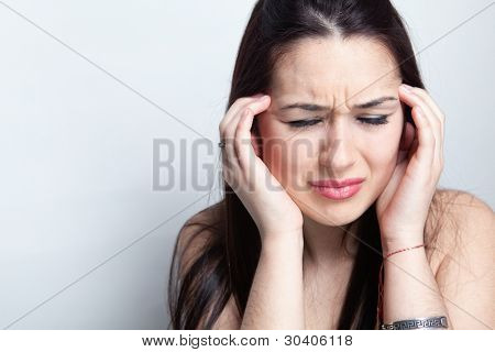 Headache concept - young woman suffering a migraine