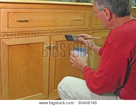 Man varnishing the base of an entertainment center