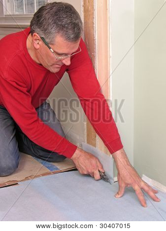 Carpenter cutting underlayment for flooring