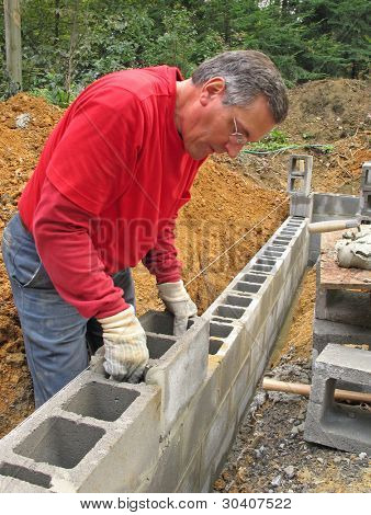 Man laying concrete block foundation wall