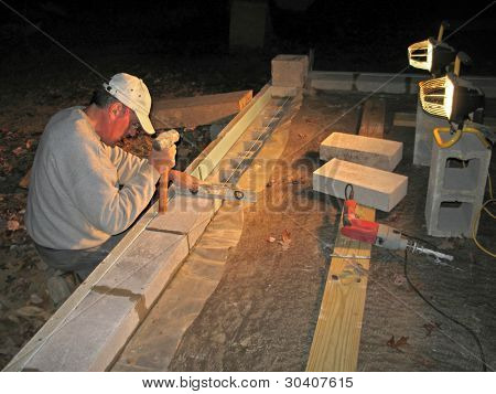 Mason laying block wall at night under lights