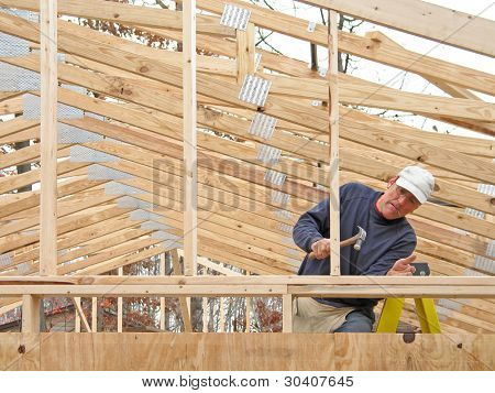 Carpenter framing gable end, with many roof trusses in background