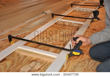 Carpenter's hand adjusting clamp on exterior trim assembly
