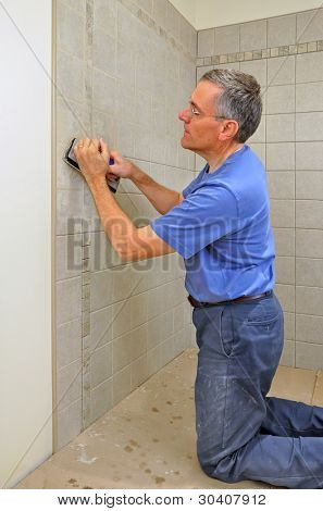 Man grouting ceramic tiles in bathroom