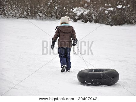 Young girl pulling inner tube up sledding hill