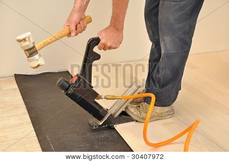 Man installing hardwood flooring with a pneumatic nailer