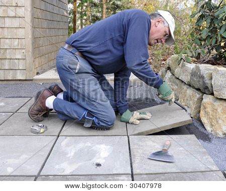 Man installs flagstone pavers on patio