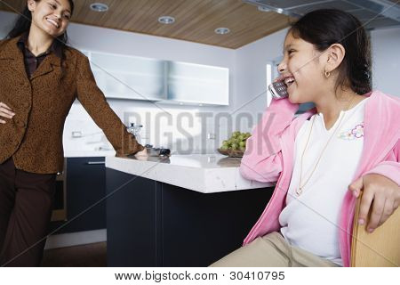 Mother with daughter talking on mobile phone