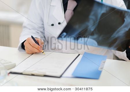 Closeup On Medical Doctor Holding Patients Roentgen And Making Note In Clipboard