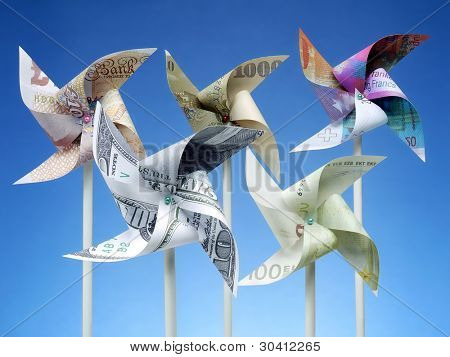Toy windmills cut from five major world currency banknotes over blue sky