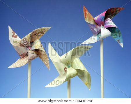 Three major European currency banknotes - Euro, Swiss Franc and British Pound cut into toy windmills shot on blue background