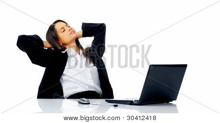 comfortable woman takes a break from her work and leans back in her office chair daydreaming about a vacation.