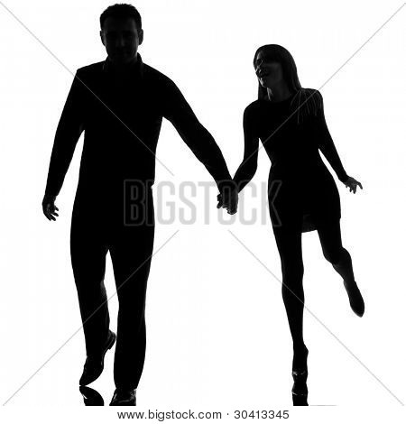 one caucasian couple man and woman running hand in hand in studio silhouette isolated on white background