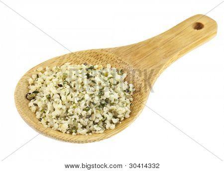 sementes de cânhamo descascadas em uma colher de bambu pequeno isolado no branco