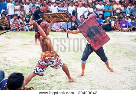 LOMBOK,INDONESIA- FEBRUARY 11: Stick fight on  February 11,2012 Lombok, Indonesia.Stick fights between villegers are an important part of the anthropological heritage of various cultures