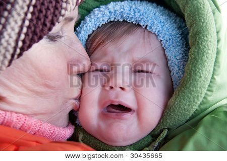 Grandmother Kissing Crying Baby.