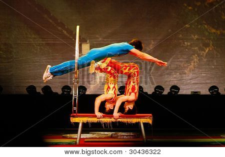 SHANGHAI, CHINA - NOVEMBER 28: A team of of gymnasts from the world famous Shanghai acrobats perform jumping act for tourist on stage on November 28, 2011 in Shanghai, China.