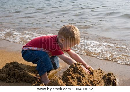 The little boy plays sand on seacoast.