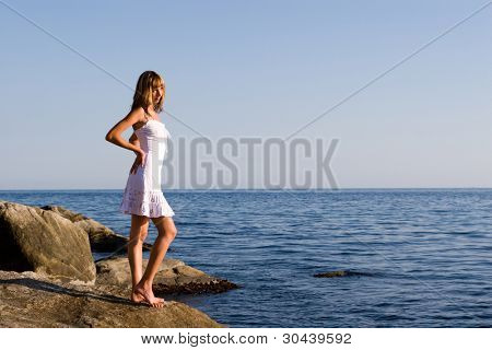 The girl stands at the sea on a decline of day.