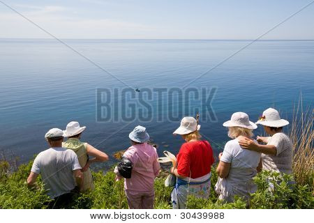 Hikers go on a slope of mountain to sea on a wild track. On the sea a fishing boat.