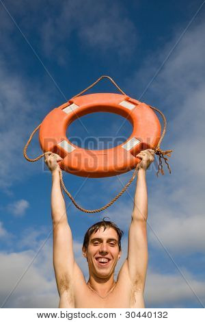 The young man holds in hands in a lifebuoy ring. On a skin of a drop of water.