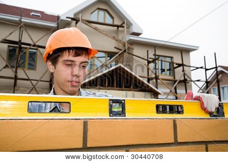 young builder checks a level of a brick wall.White sky