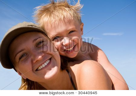 Mother and the child (son) on a beach in summer day.