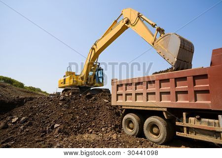 The excavator loads a truck an earthen ground