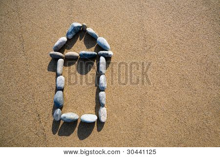 picture of a house from a pebble on sand.