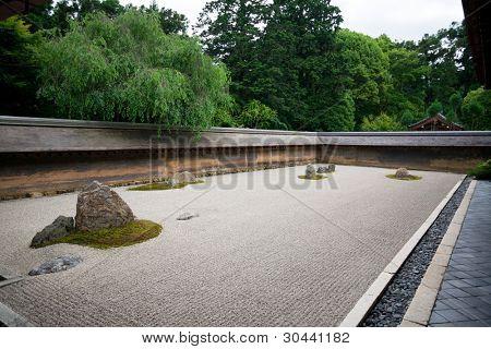 A Zen Rock Garden in Ryoanji Temple.In a garden fifteen stones on white gravel. Kyoto.Japan.Evening.