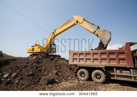 Excavator loads a truck an earthen ground