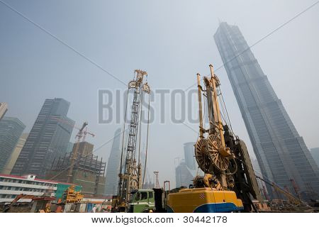 Shanghai city. China. In the foreground the beginning of construction of new office building. June, 2009.