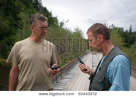 Hikers check the operating status of walkie-talkie in field conditions.