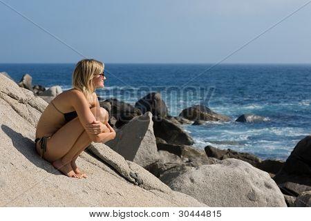 Garota atraente relaxante em uma bela praia rochosa junto ao mar.