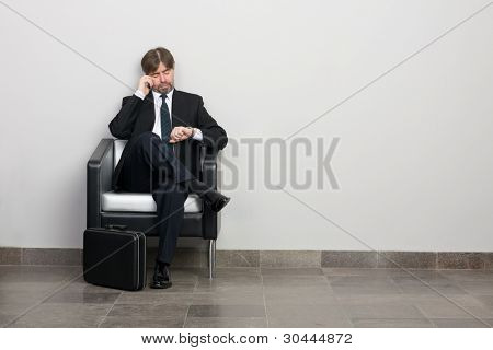 Businessman talking on a mobile and looking at your watch.