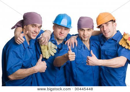 A friendly young team of construction workers shows thumbs sign okay.
