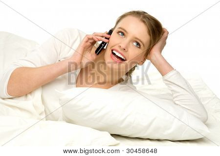 Young female in bed with a mobile phone