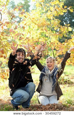 man and woman throwing leaves