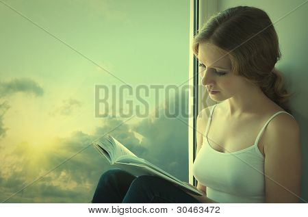Beautiful Young Woman Reading A Book While Sitting At A Window In The Sunset