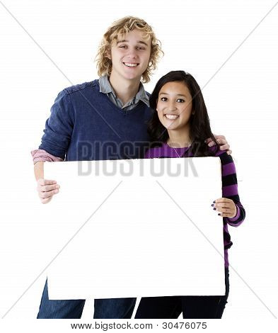 happy teens holding a blank sign