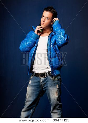 Young Man Listening Music With Headphones Standing On Blue Background