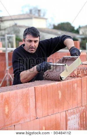 Man gießt nassen Zement an Wand